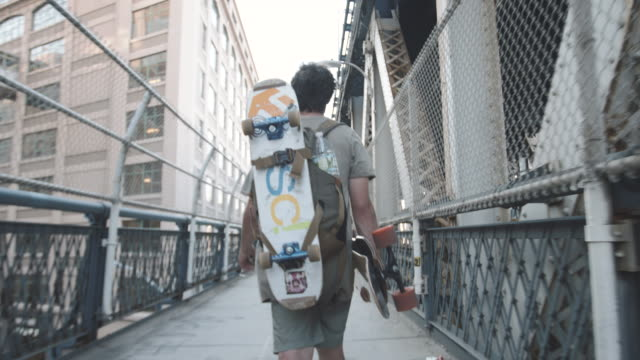 b roll shot of a skateboarder walking over nyc's manhattan bridge. - roll over stock videos and b-roll footage