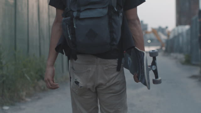 vidéos et rushes de b roll shot of a young, mixed race man sneaking into a secret skate spot in brooklyn, nyc - sac à dos