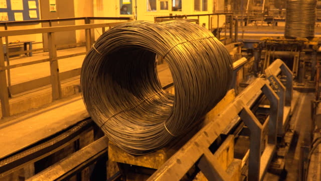 vídeos de stock e filmes b-roll de rolled metal wire being conveying at metallurgical factory - aço
