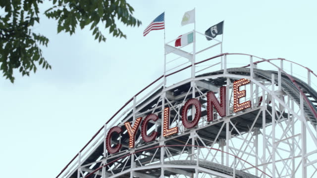 a roller coaster passes on a summer afternoon in coney island, brooklyn. - coney island stock-videos und b-roll-filmmaterial