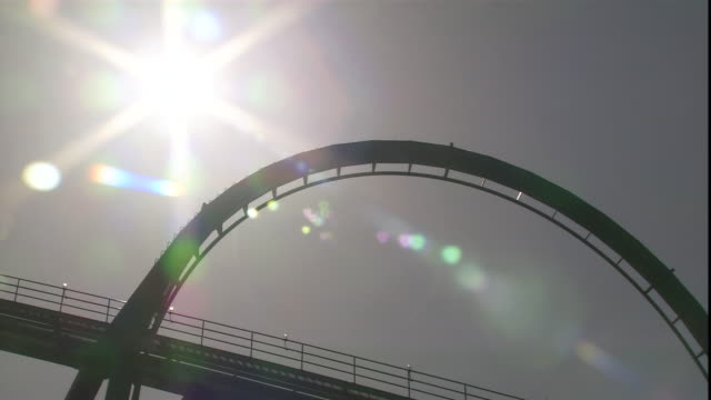 a roller coaster travels upside down through a loop. - loopable moving image stock videos & royalty-free footage