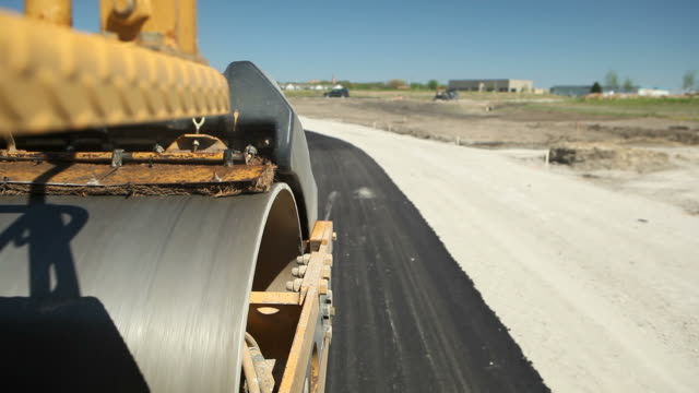 roller compactor on fresh asphalt road - road construction stock videos and b-roll footage