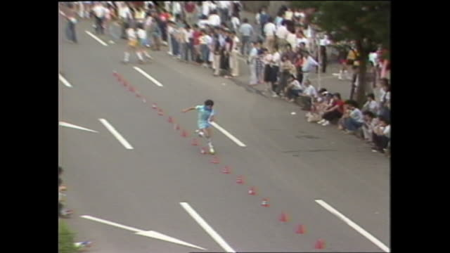 A roller skater zigzags through orange cones on a pedestrian paradise in Japan.