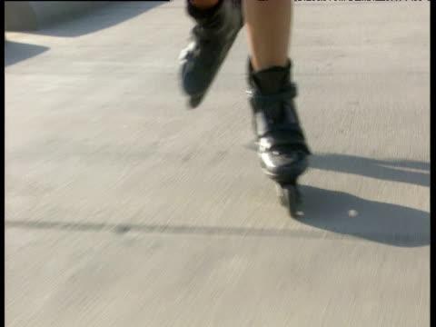 rollerblader skates along concrete promenade towards camera venice beach - blade stock videos & royalty-free footage