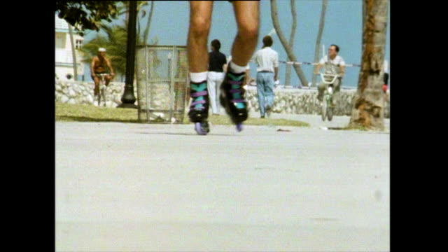 cu of rollerblades skating on miami boardwalk; 1991 - di archivio video stock e b–roll