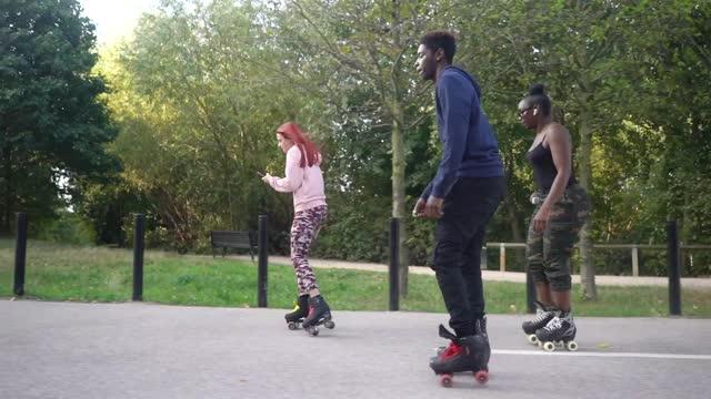 rollerskating friends skating along a pedestrian walkway - balance stock videos & royalty-free footage