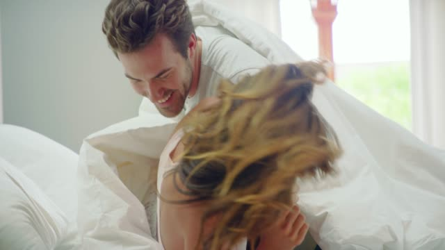 rolling around in the sheets - heterosexual couple stock videos & royalty-free footage