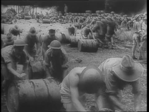 rolling barrels from the fuel dump / dropping off barrels of gasoline by plane / douglas c17 army transport plane on airfield / men unloading oil... - ドラム容器点の映像素材/bロール