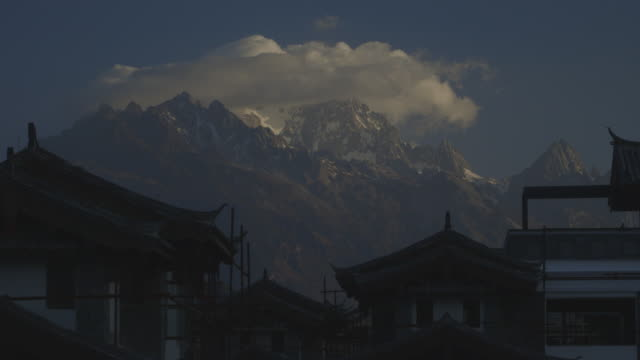 a rolling cloud forms from snow on the jade dragon snow mountain behind the 'artichoke leaf' rooves of the historic city of lijiang, yunnan province, china, at daybreak. - jade stock videos & royalty-free footage