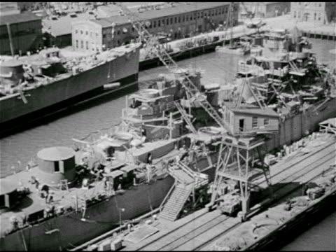 stockvideo's en b-roll-footage met rolling crane moving in grooves along dock next to ship vs men working on ship cleaning torpedo ws battleship docked w/ guns raised crane bg note... - 1943