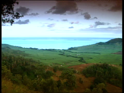 Rolling fields down to bright blue sea pan to mountains and sun tinged clouds. Mauritius