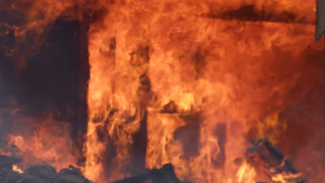 rolling flames consume an interior wall of a burning house and debris falls from above - explosion wall stock videos and b-roll footage