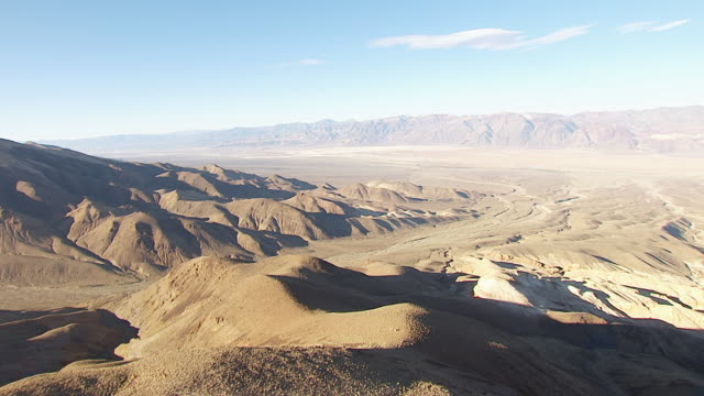 ws aerial pov rolling foothills and dry river beds in death valley with mountains in background / california, united states - riverbed stock videos & royalty-free footage