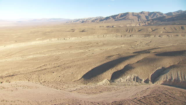 ws aerial pov rolling foothills and dry river beds in death valley with mountains in background / california, united states - 川床点の映像素材/bロール