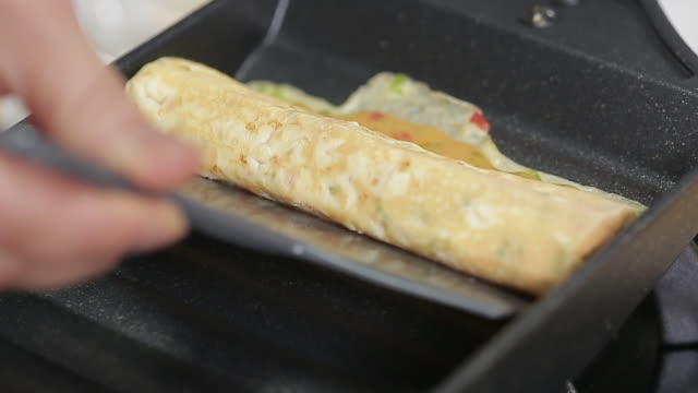 vídeos de stock e filmes b-roll de rolling gyeran-mari (korean rolled omelette) with cheese - rolar