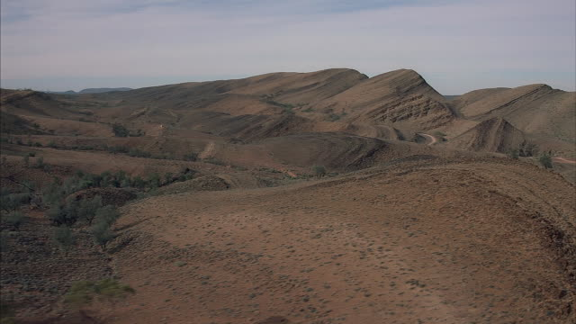 Rolling hills spread out over a desert in Australia.