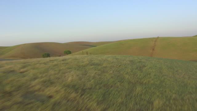 ws aerial pov rolling hills with fence during sunset at sacramento valley, california - kulle bildbanksvideor och videomaterial från bakom kulisserna