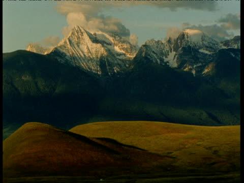 rolling hills with mountains behind, north dakota - ムラがある点の映像素材/bロール