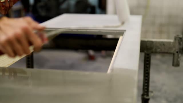 rolling on sealant to concrete work piece in workshop - sigillante video stock e b–roll