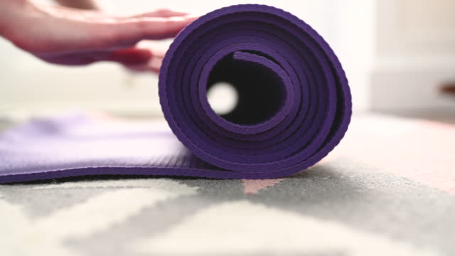 rolling out yoga mat - one mid adult woman only stock videos & royalty-free footage