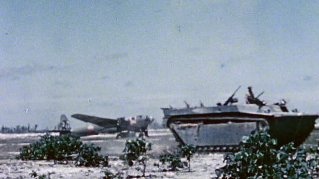 rolling past parked c-47, and smoke rising from burning c-47 / peleliu, palau - amphibious vehicle stock videos & royalty-free footage