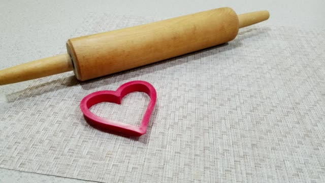 rolling pin and heart shaped cookie cutter on kitchen counter. - rolling pin stock videos & royalty-free footage