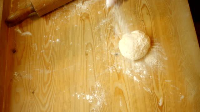 Rolling pin flattening a knead on a wooden table.