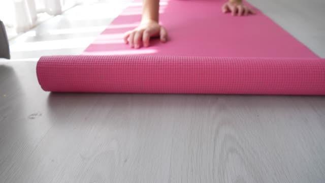 床にピンクのヨガマットを転がします。 - エクササイズマット点の映像素材/bロール