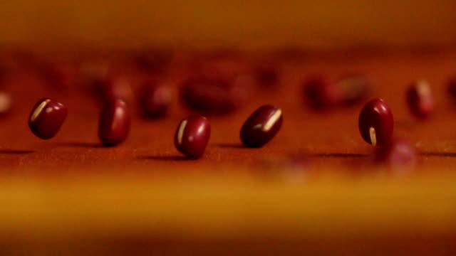 Rolling red adzuki beans in slow motion shot