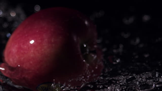 rolling red apples triple falling into water, black background - リンゴ点の映像素材/bロール