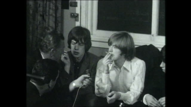 stockvideo's en b-roll-footage met rolling stones sydney airport terminal presser all seated on lounge hear screaming fans / 7 reporter with mick jagger brian jones down one end of... - 1965