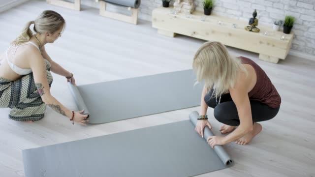 vídeos de stock, filmes e b-roll de arregaçando seus tapetes de yoga - boa postura