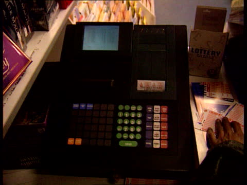 roll-over lottery ticket sales; lib england: london: wardour street: lottery machine as ticket being printed: side male customer handing over lottery... - lottery stock videos & royalty-free footage