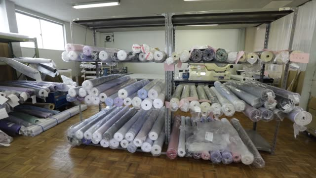 rolls of cloth used for making original stitch shirts sit at a factory operated by koyama choya sewing corp., a subsidiary of yamaki co., in saku,... - top capo di vestiario video stock e b–roll