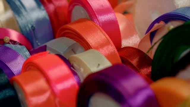 vídeos de stock, filmes e b-roll de rolos de fitas de seda multicoloridos na loja de tecidos - rolo