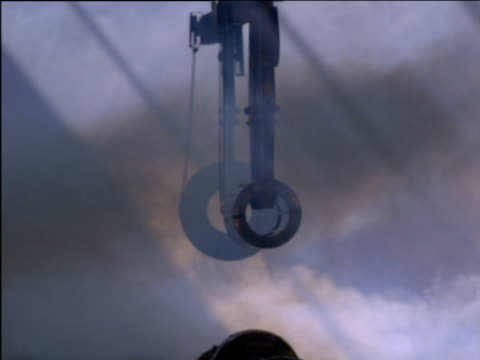 stockvideo's en b-roll-footage met rolls of steel held by cranes move through steamy warehouse in steel mill, south africa - hijsen