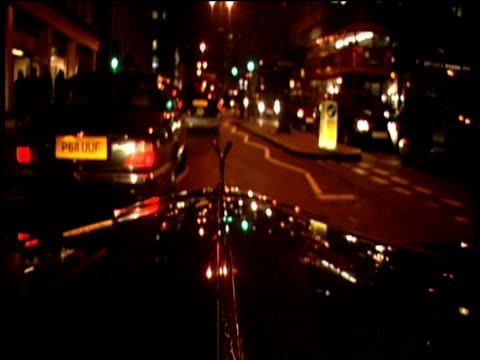 rolls royce travelling through fitzrovia city lights reflected on windscreen parks at curbside london. - rolls royce stock videos and b-roll footage
