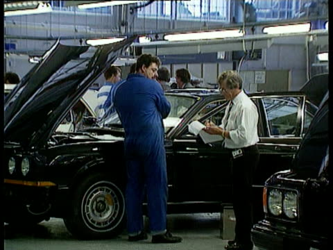 rolls-royce cars in factory / mechanics working on cars / engine / hoods up on several cars. rolls-royce cars in production on november 04, 1994 in... - rolls royce stock videos & royalty-free footage