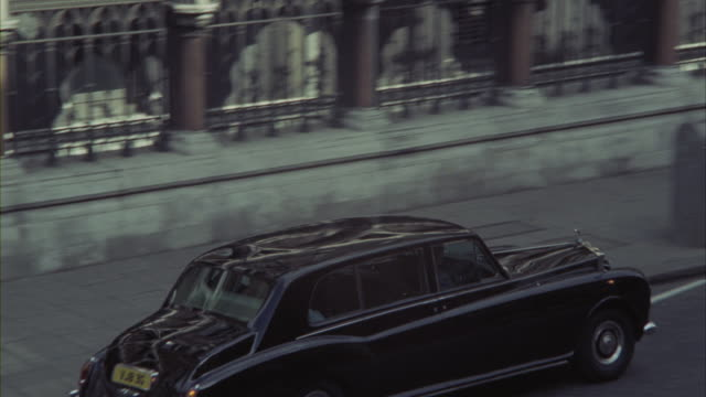 a rolls-royce passes in front of a courthouse, followed by other traffic including double-decker buses. - rolls royce stock videos and b-roll footage