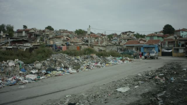 vidéos et rushes de roma settlement in bulgaria, litter in streets, people watching - bidonville