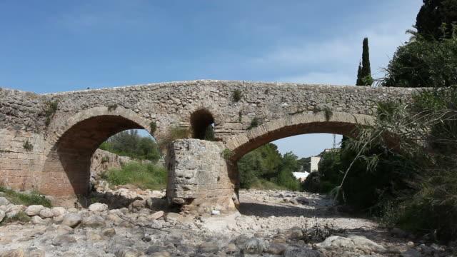 vídeos y material grabado en eventos de stock de puente romano en pollenca/mallorca - piedra material de construcción
