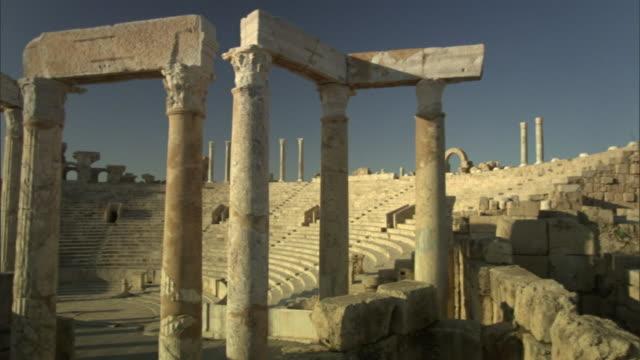 vidéos et rushes de roman columns stand in a ruined arena at leptis magna,  libya. - rome antique