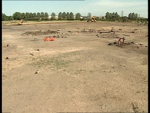 vidéos et rushes de roman excavation threatened by redevelopment bv workers walking away down track with wheelbarrows scoop of earthmover lifting soil ms driver in cab... - turning on or off