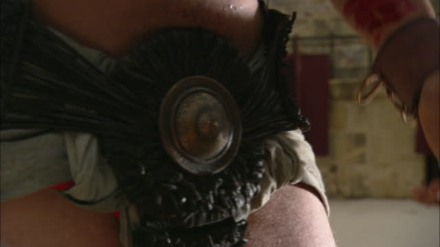 vídeos de stock, filmes e b-roll de a roman gladiator wipes blood from his sword onto his arm. - reconstituição histórica