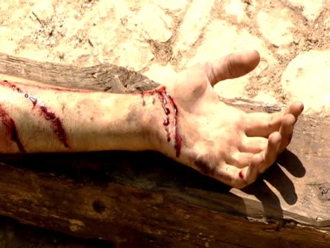 vídeos de stock, filmes e b-roll de roman guard prepares to nail jesus' arm to the cross. - cruz objeto religioso