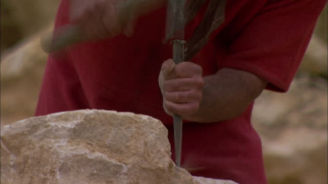 a roman soldier chisels a rock. - historical reenactment stock-videos und b-roll-filmmaterial