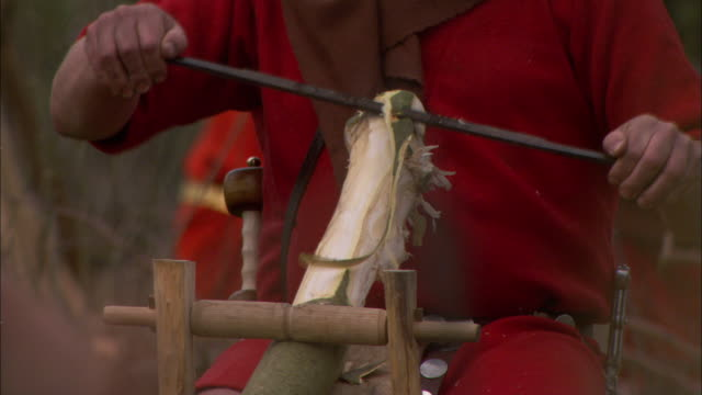 a roman soldier peels bark from a log. - historical reenactment stock-videos und b-roll-filmmaterial