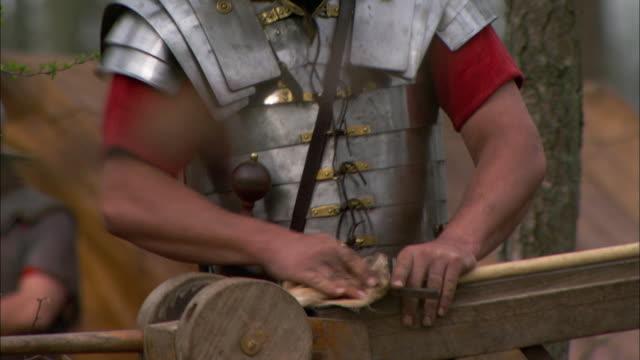 vídeos y material grabado en eventos de stock de a roman soldier sands a piece of equipment. - soldado romano