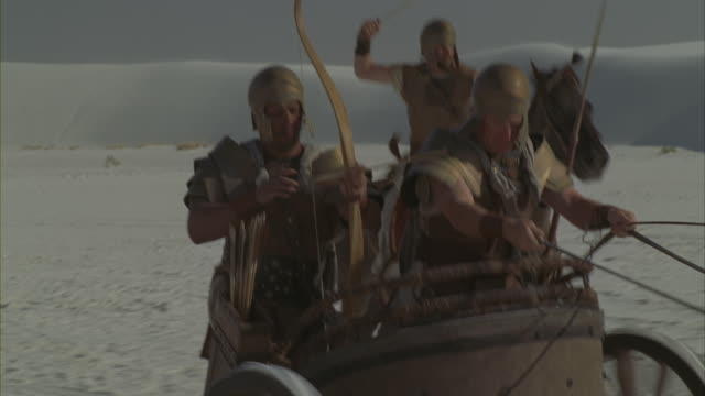 vídeos de stock, filmes e b-roll de a roman soldier shoots an arrow as he rides a chariot across a desert. - roman soldier