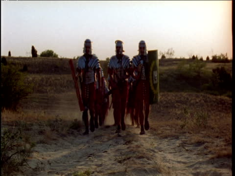 roman soldiers approach and pass by on dusty road hungary - römisch stock-videos und b-roll-filmmaterial